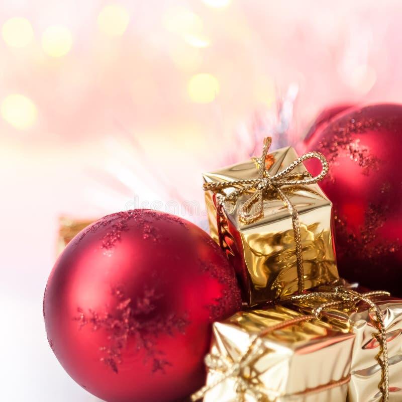 Natal feliz, ano novo, presentes nas caixas do ouro, bolas vermelhas do Natal no canto direito Fundo Bokeh imagens de stock