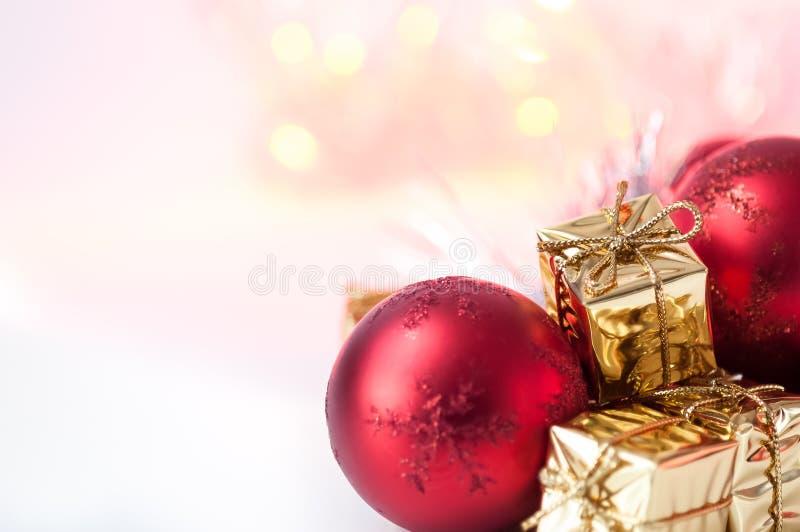 Natal feliz, ano novo, presentes nas caixas do ouro, bolas vermelhas do Natal no canto direito Fundo Bokeh foto de stock royalty free