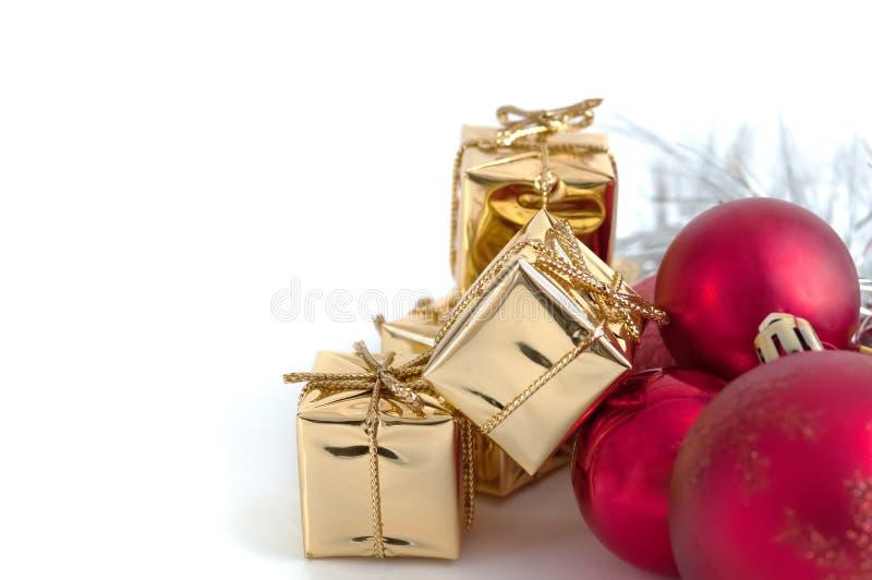 Natal feliz, ano novo, presentes nas caixas do ouro, bolas vermelhas do Natal no canto direito Fundo branco imagens de stock royalty free