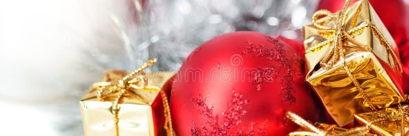 Natal feliz, ano novo, presentes nas caixas do ouro, bolas vermelhas do Natal no canto direito Fundo branco imagem de stock royalty free