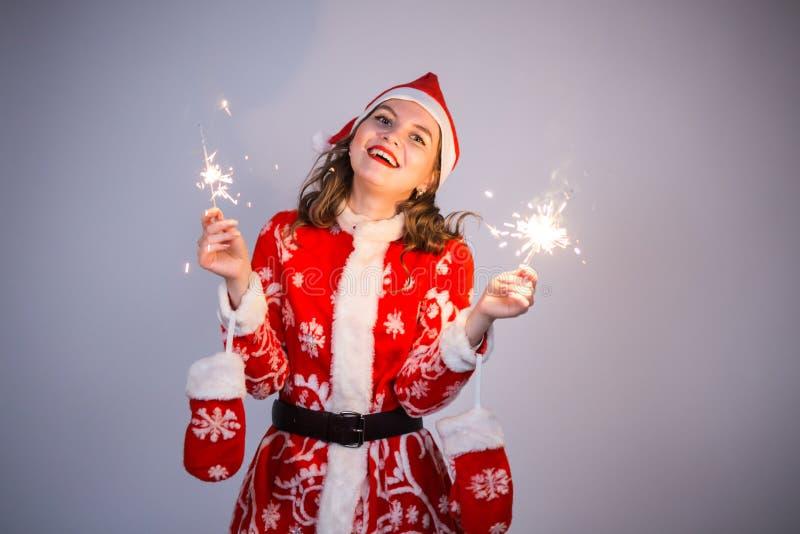 Natal, feriados e conceito dos povos - mulher no terno de Santa com riso das luzes e dos sparkles foto de stock royalty free
