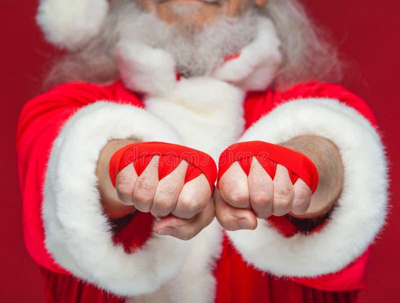 Natal Fim acima de dois punhos de Santa Claus com uma ferida vermelha da atadura neles para encaixotar Kickboxing, encaixotamento imagens de stock