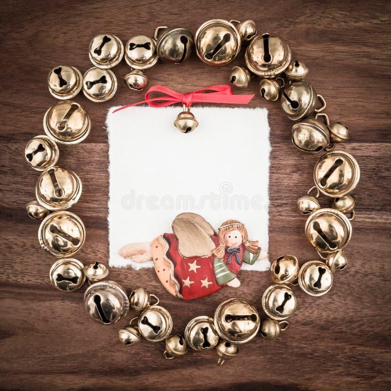 Natal, grinalda, sinos, anjo, etiqueta do presente na madeira fotos de stock royalty free