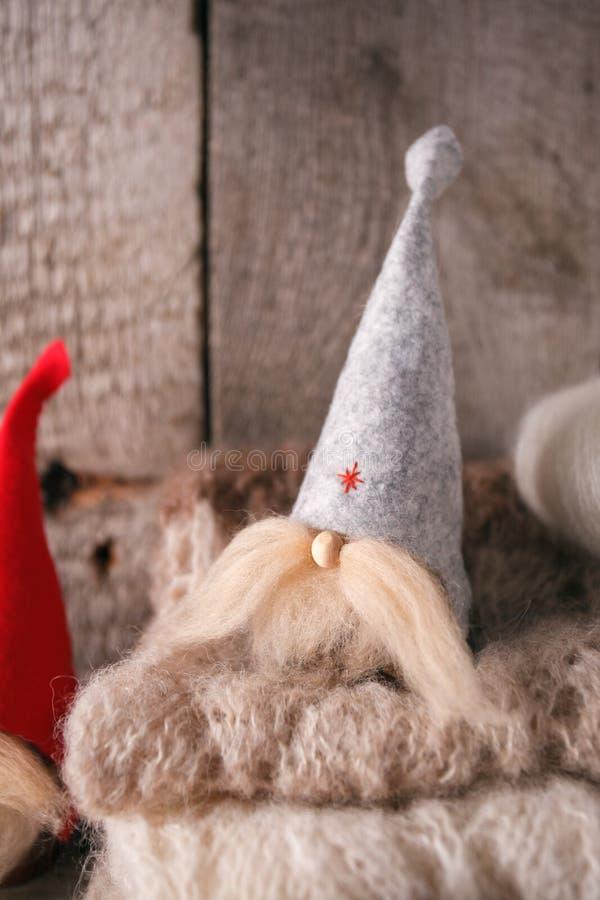 Natal interior com gnomos decorativos, len?o morno da malha no fundo de madeira das pranchas Composi??o do inverno do ano novo, i imagens de stock royalty free