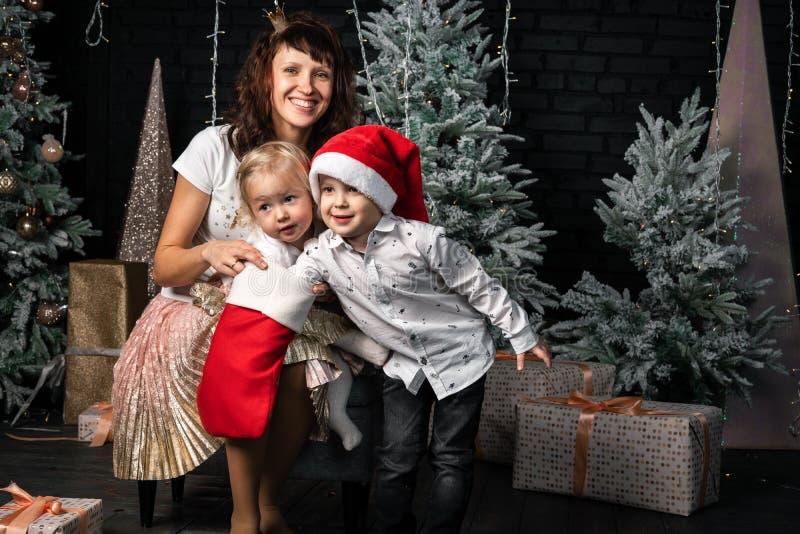 Natal: A mamã no tampão de Santa com seus filho e filha verificará os presentes em uma peúga vermelha fotos de stock royalty free