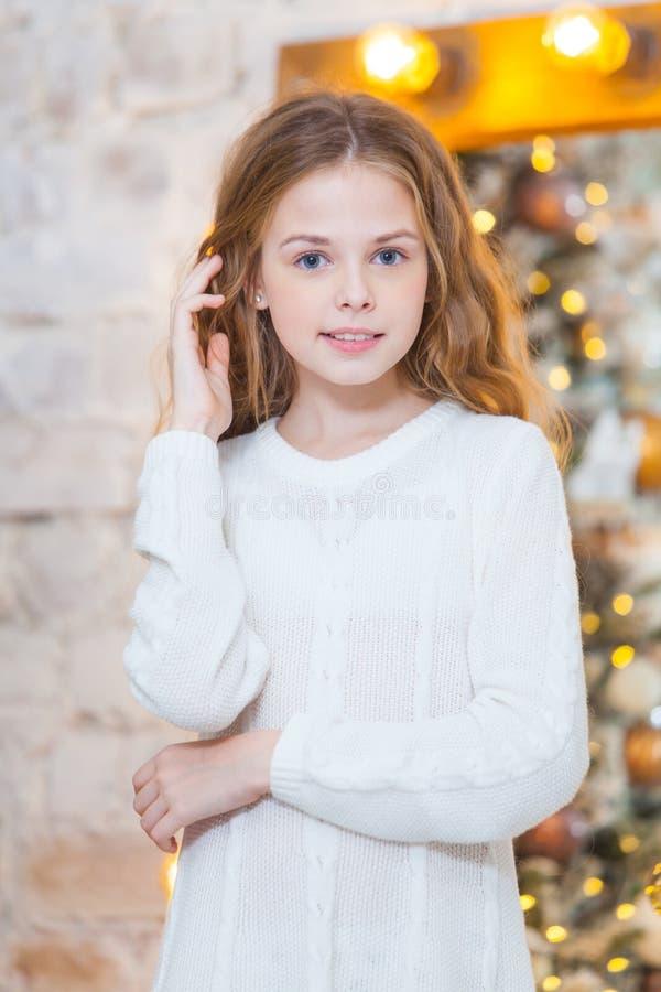 Natal Menina de sorriso bonita Sobre a árvore de Natal ilumina o fundo Ano novo feliz imagens de stock royalty free