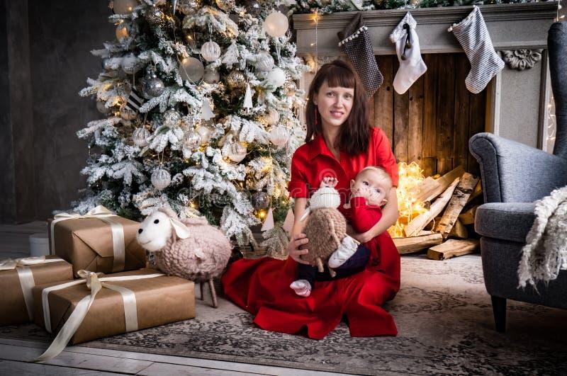 Natal no círculo de família: uma mãe nova em um vestido vermelho está sentando-se perto da árvore de Natal e está guardando-se um fotografia de stock