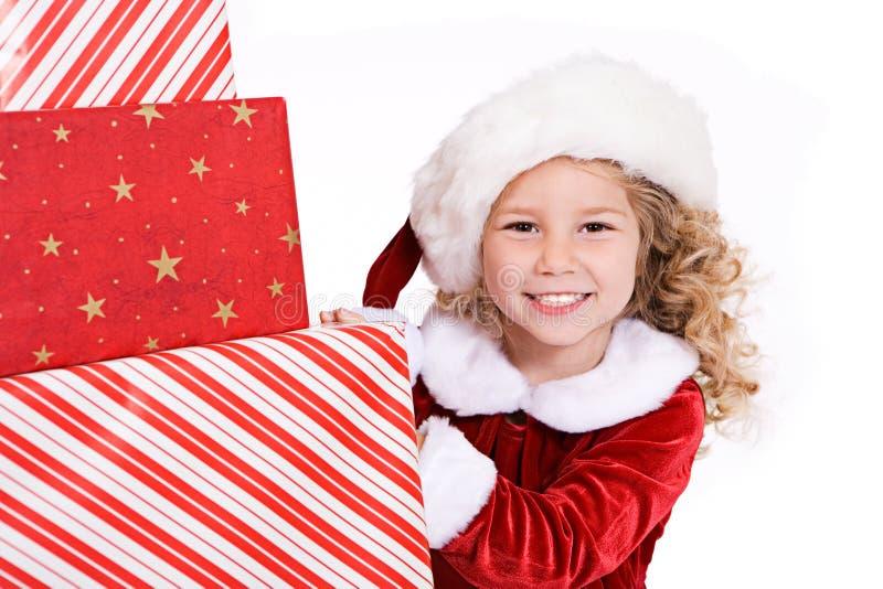 Natal: Pilha de Santa Girl Peeks Around Big de Natal Presen fotos de stock royalty free