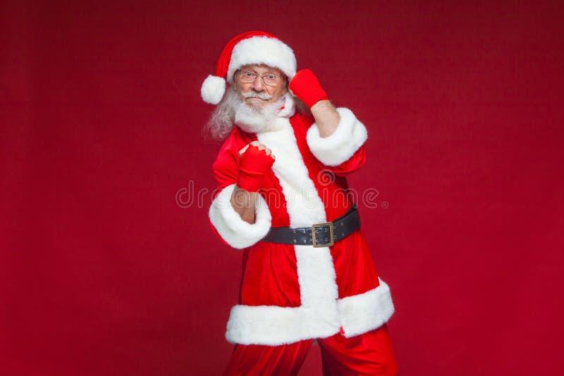 Natal Santa Claus com ataduras vermelhas fere-se em suas mãos para encaixotar imita pontapés Kickboxing, karaté, encaixotando foto de stock