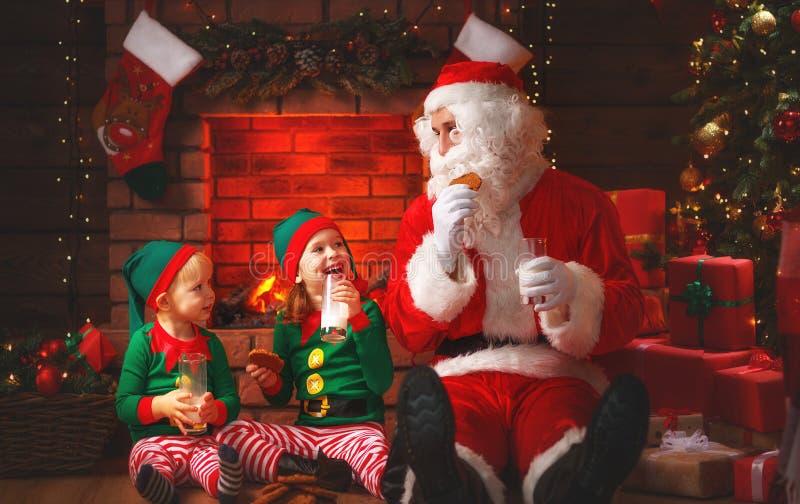 Natal Santa Claus com leite da bebida dos duendes e come cookies imagens de stock royalty free
