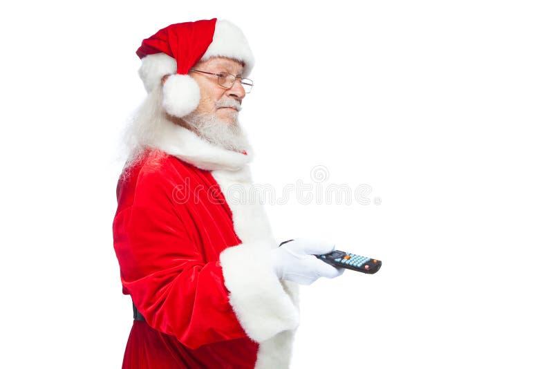 Natal Santa Claus nas luvas brancas que mantêm uma tevê de controle remoto Consulte listas da tevê do Natal, selecione o canal foto de stock royalty free