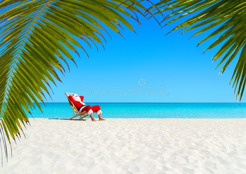 Natal Santa Claus que relaxa no sunlounger na praia tropical arenosa do oceano imagem de stock