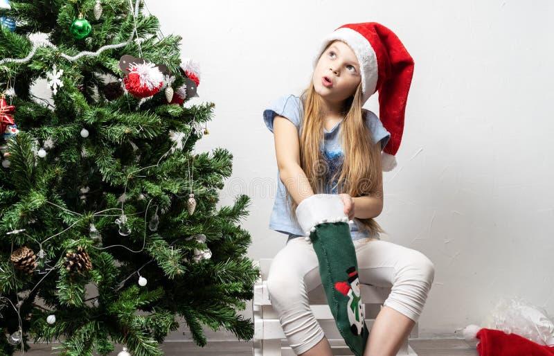 Natal: Uma criança da menina em um tampão vermelho senta-se perto de uma árvore com brinquedos e cola-se sua mão em uma grande pe fotografia de stock