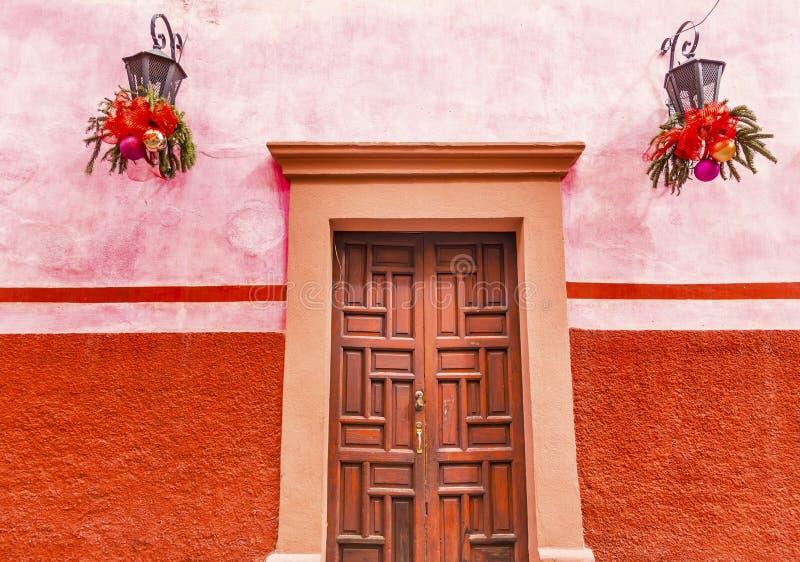 Natal vermelho cor-de-rosa San Miguel Allende Mexico da porta de Brown da parede imagem de stock royalty free