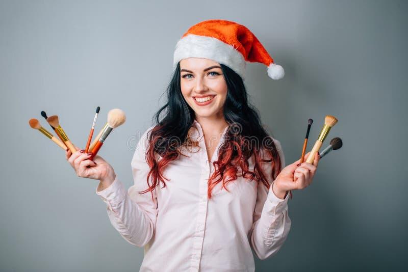 Natal vestindo Santa Hat do maquilhador da mulher fotos de stock royalty free