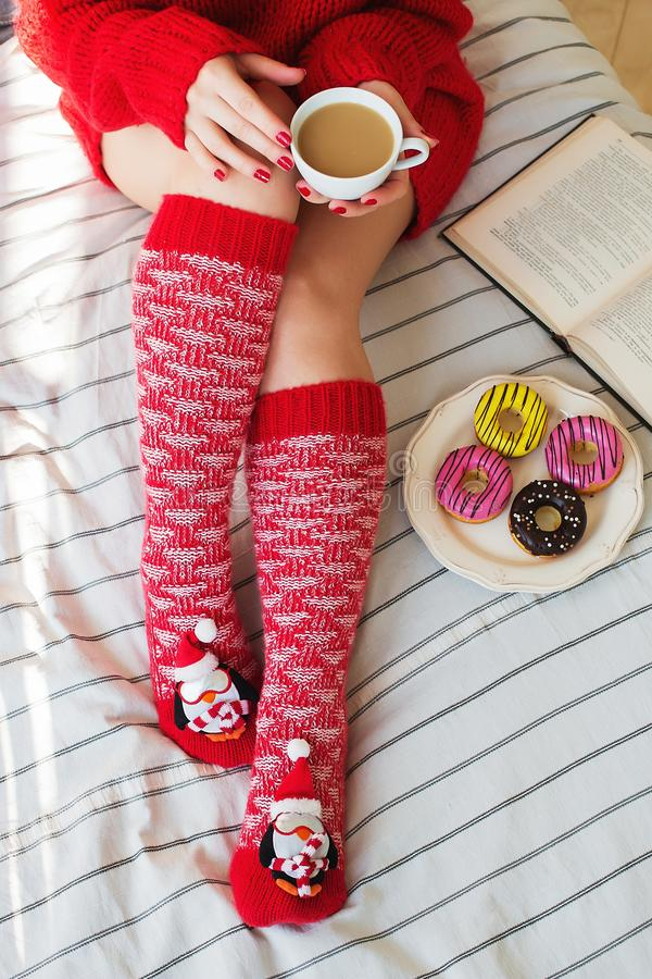 Natale accogliente a casa Piedi del ` s delle donne in calze di Natale, grande presente, tazza di tè, caramella e cioccolato dei  immagini stock