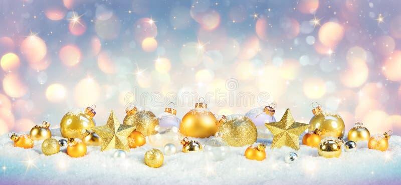 Natale - bagattelle dorate su neve immagini stock