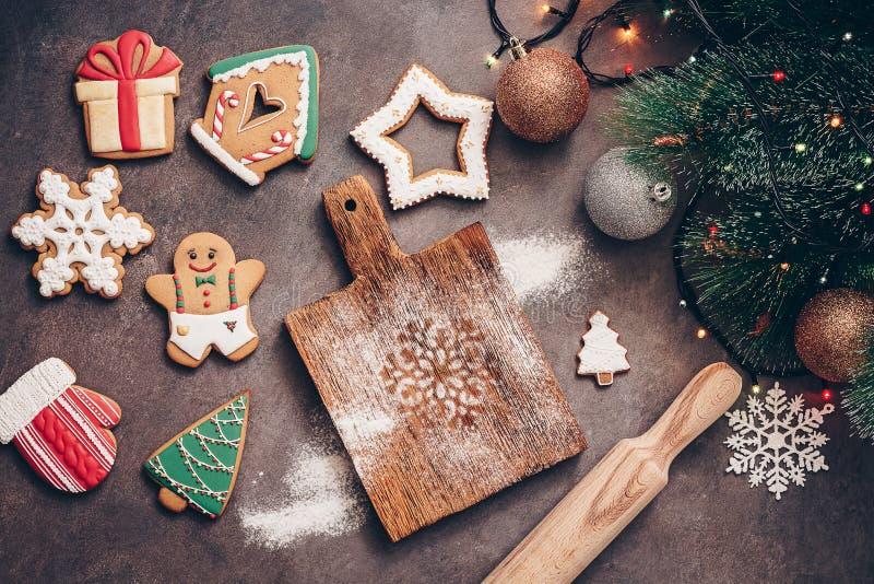 Natale che cuoce fondo Vario zenzero ha lustrato il pan di zenzero, un ramo del pino e una ghirlanda su un fondo rustico scuro to fotografie stock