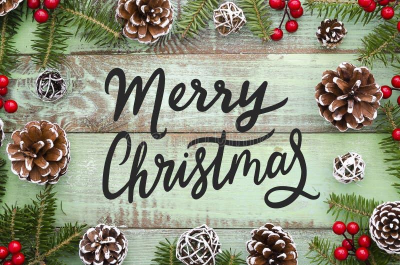 Natale che segna sul fondo di legno con la pigna di Natale, rami dell'abete, decorazioni rosse Natale e buon anno immagini stock
