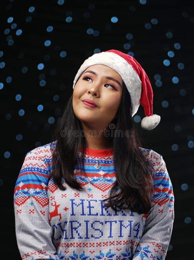 Natale d'uso maglione e Santa Hat della ragazza asiatica su incandescenza scura fotografia stock