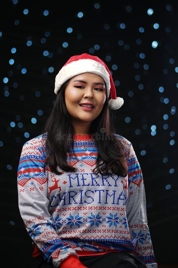 Natale d'uso maglione e Santa Hat della ragazza asiatica su incandescenza scura fotografie stock
