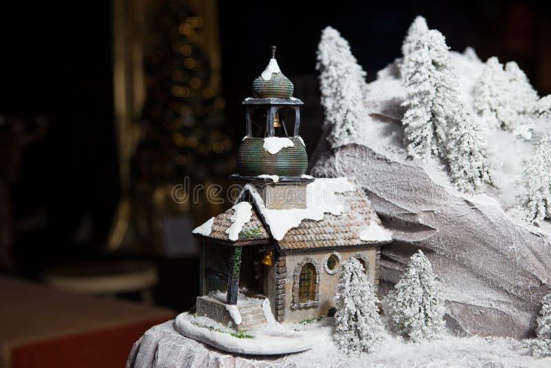 Natale, decorazione da ceramica, cappella della chiesa ortodossa del giocattolo nella neve vicino alle rocce ed alberi fotografia stock
