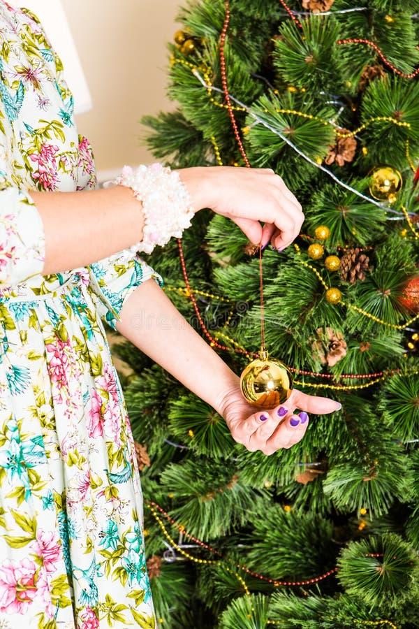 Natale, decorazione, feste e concetto della gente - vicino su della palla di natale della tenuta della mano della donna fotografia stock