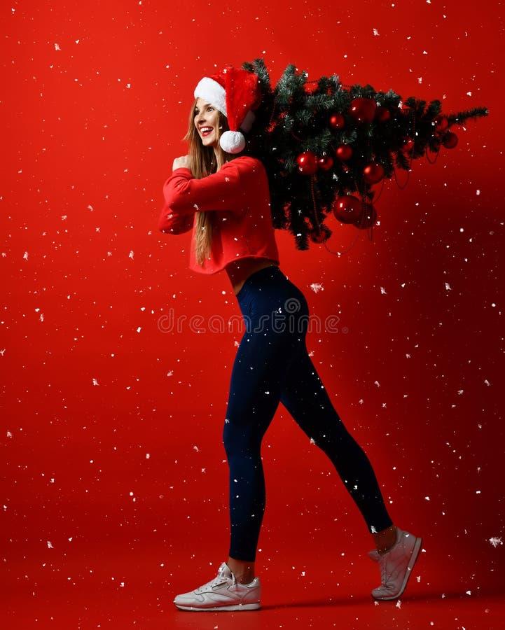 Natale del cappello di Santa che mette in mostra donna che tiene l'albero di natale sulle sue spalle Energia del vincitore lui fo fotografie stock