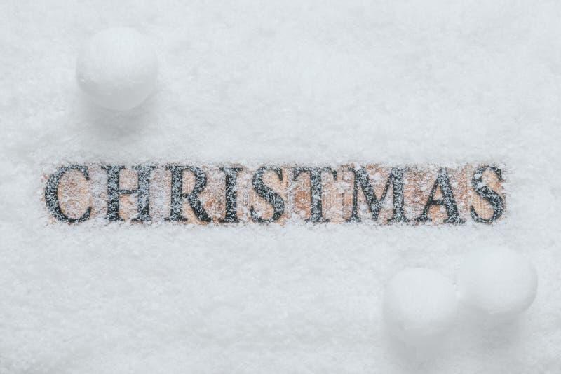 Natale di parola in neve con le palle di neve immagine stock