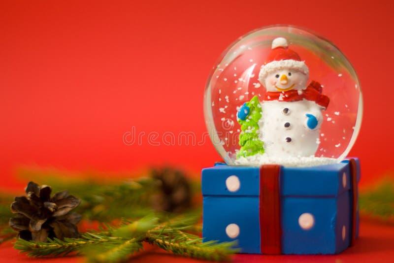 Natale e carta del nuovo anno con il pupazzo di neve del globo della neve dentro Contenitore di regalo su priorità bassa rossa Fe immagine stock libera da diritti