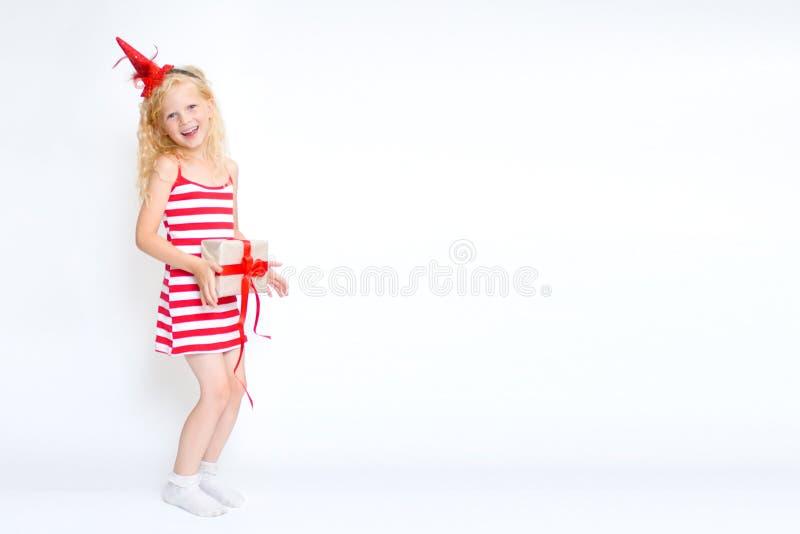 Natale e carta del nuovo anno con la piccola ragazza bionda sveglia felice in vestito rosso e bianco dal costume di carnevale con fotografia stock libera da diritti