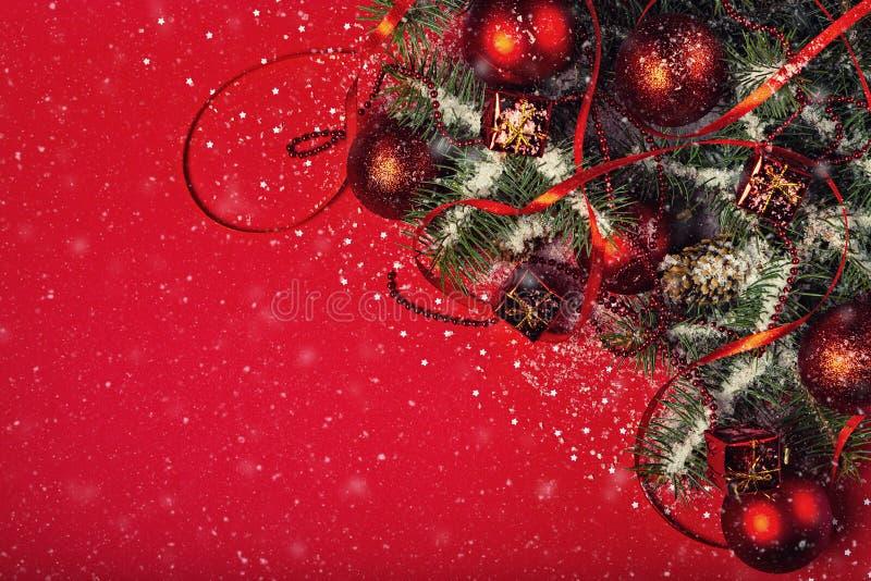 Natale e composizione in feste del nuovo anno su fondo rosso con lo spazio di caduta della copia e della neve per il vostro testo fotografie stock libere da diritti