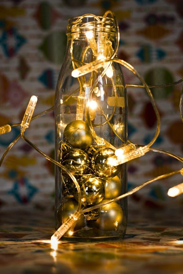 Natale e decorazione del nuovo anno con la bottiglia di vetro e la ghirlanda nella tonalità d'annata immagine stock libera da diritti