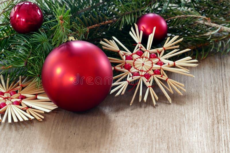 Natale e decorazione del nuovo anno con le bagattelle e lo sta rossi della paglia fotografia stock