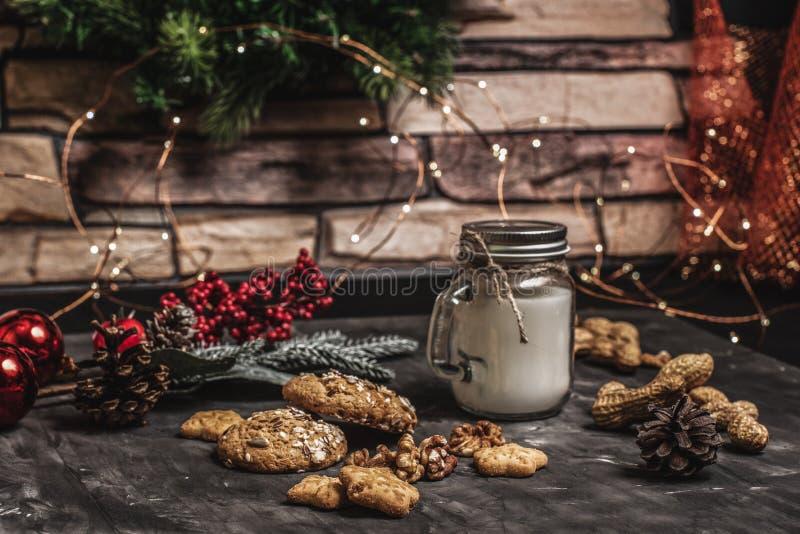 Natale e fondo della decorazione della tavola del nuovo anno con la ghirlanda, i biscotti, le pigne, i wallnuts e la candela in t immagini stock libere da diritti