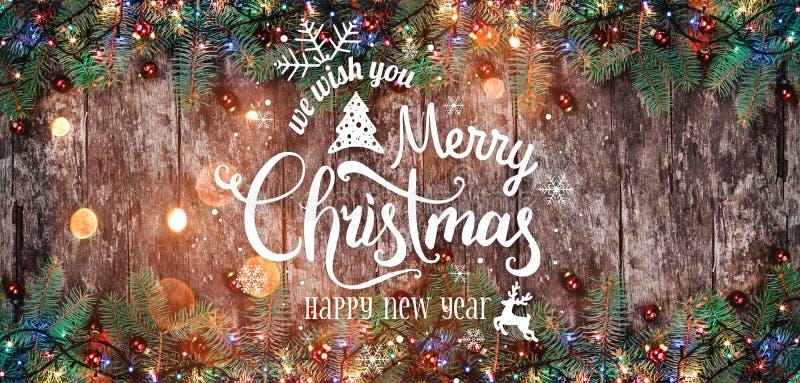 Natale e nuovo anno tipografici su fondo di legno con i rami dell'abete immagini stock