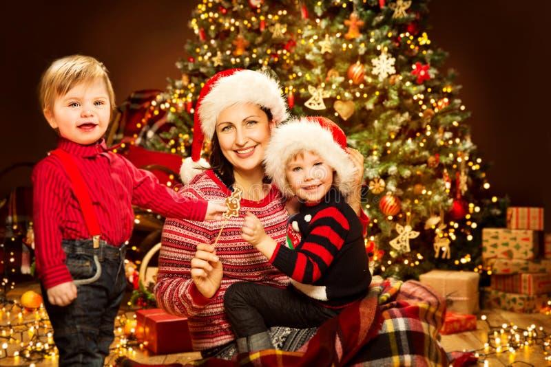 Natale famiglia, madre con la parte anteriore dei bambini delle luci dell'albero di natale, mamma felice e bambino immagini stock libere da diritti