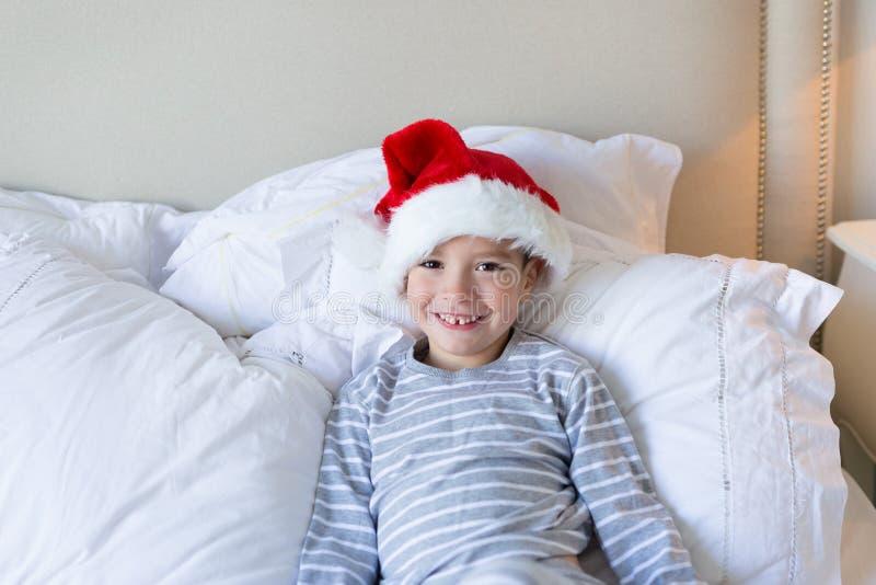 Natale felice e nuovo anno Il ragazzo sorridente felice in cappello rosso di Santa si siede a letto dell'interno Concetto anno di fotografia stock