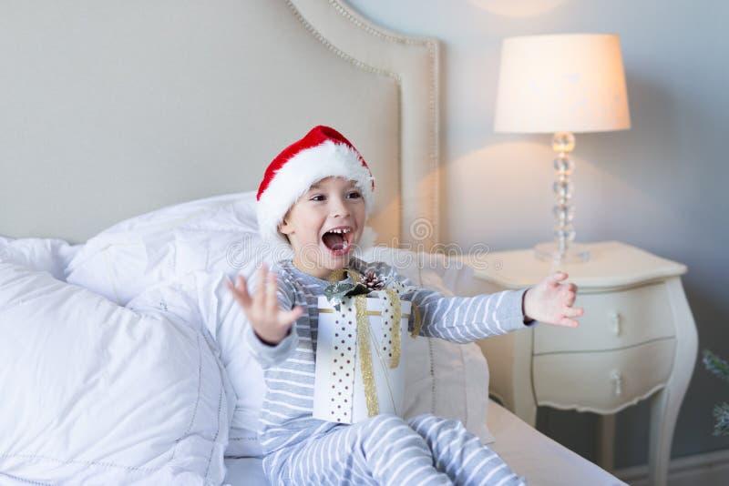 Natale felice e nuovo anno Il ragazzo sorridente felice in cappello rosso di Santa si siede a letto tenendo la scatola attuale de fotografie stock libere da diritti