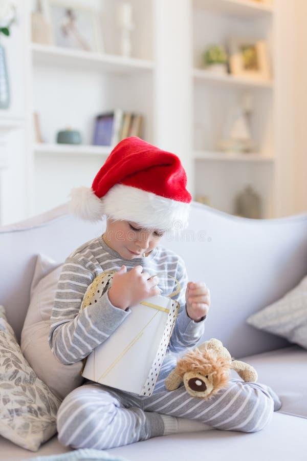 Natale felice e nuovo anno Il ragazzo sorridente felice in cappello rosso di Santa si siede a letto tenendo la scatola attuale de fotografia stock libera da diritti