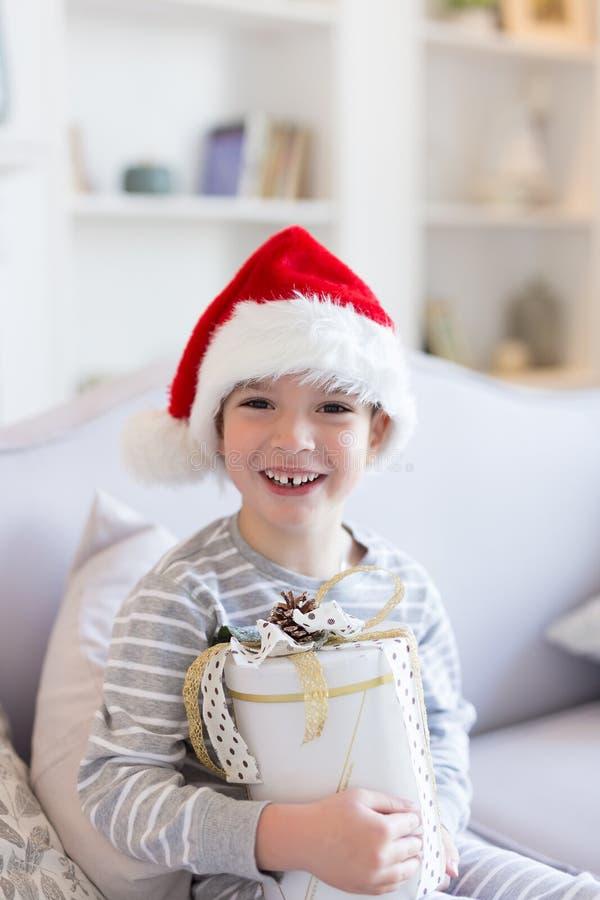 Natale felice e nuovo anno Il ragazzo sorridente felice in cappello rosso di Santa si siede a letto tenendo la scatola attuale de fotografia stock