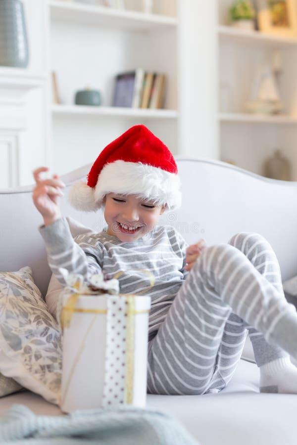 Natale felice e nuovo anno Il ragazzo sorridente felice in cappello rosso di Santa si siede sul sofà che tiene la scatola attuale fotografia stock