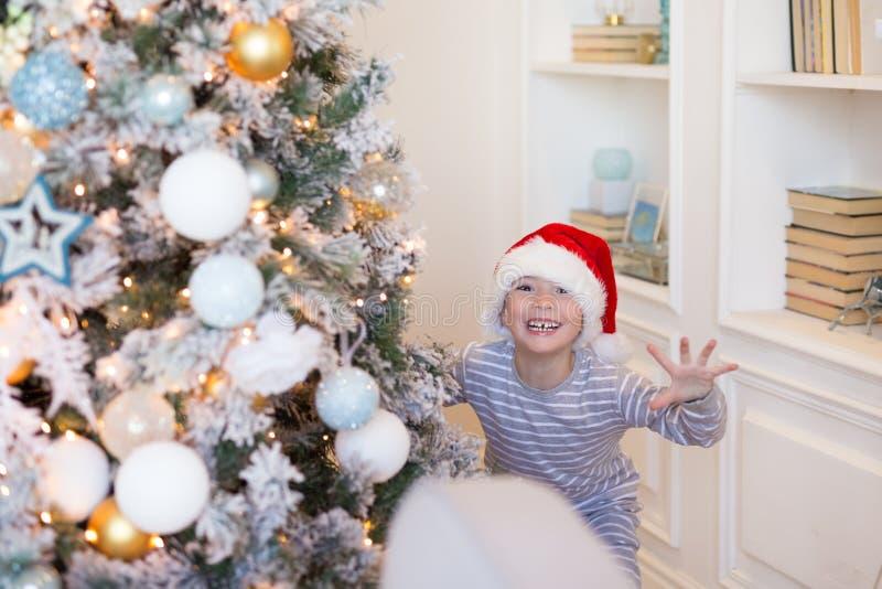 Natale felice e nuovo anno Ragazzo sorridente felice nello sguardo rosso di Santa sorprendente dall'albero di Natale dell'interno immagine stock