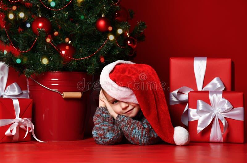 Natale felice e nuovo anno Ritratto del bambino in regali aspettanti di Natale del cappello rosso di Santa immagine stock