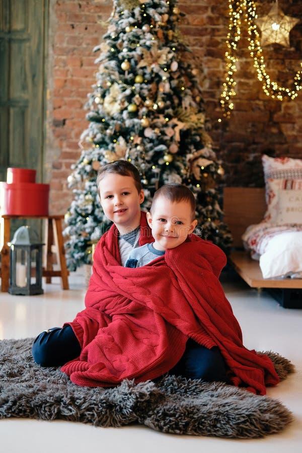 Natale, feste e concetto di infanzia - fratelli felici che si siedono sul pavimento, sognando, Santa aspettante fotografie stock libere da diritti