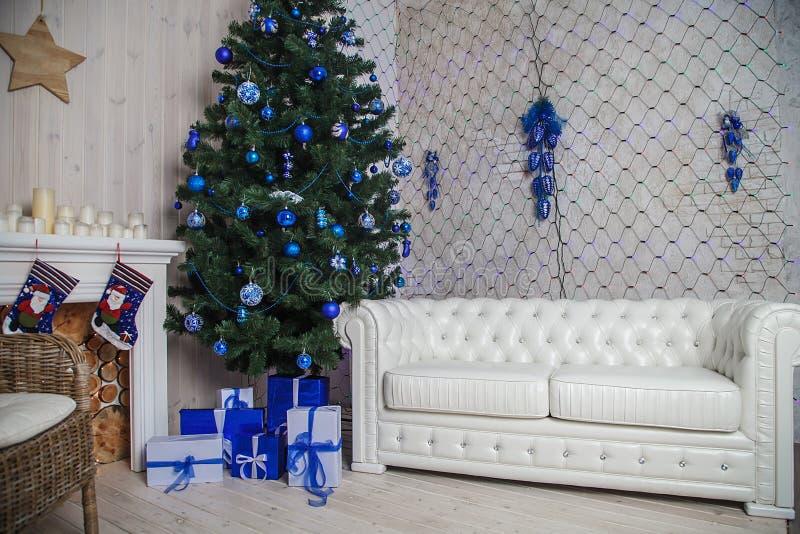 Natale interno con il sofà ed il camino bianchi nel colore blu fotografia stock