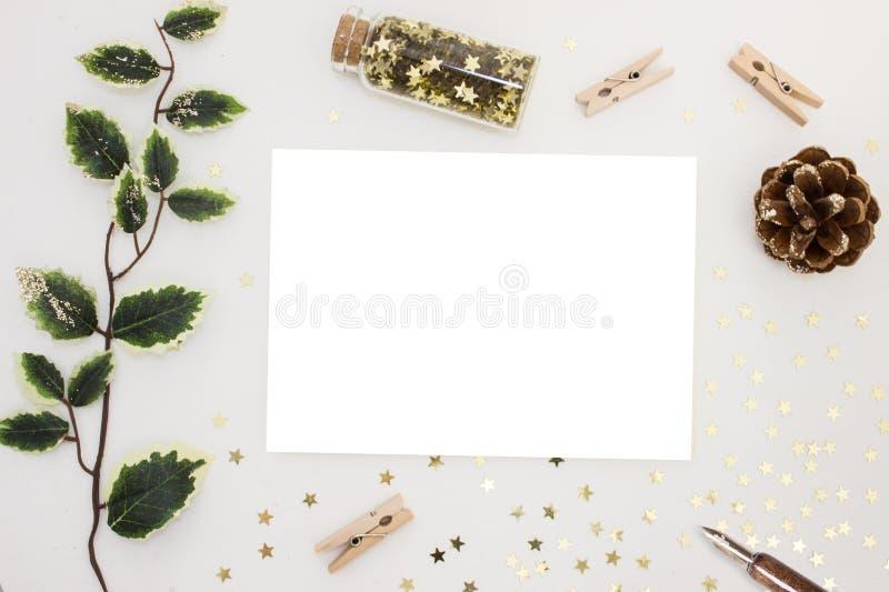 Natale magico Modello dell'insegna dell'invito della carta in bianco, cancelleria festiva e decorazioni, stelle dorate, ramo verd fotografie stock