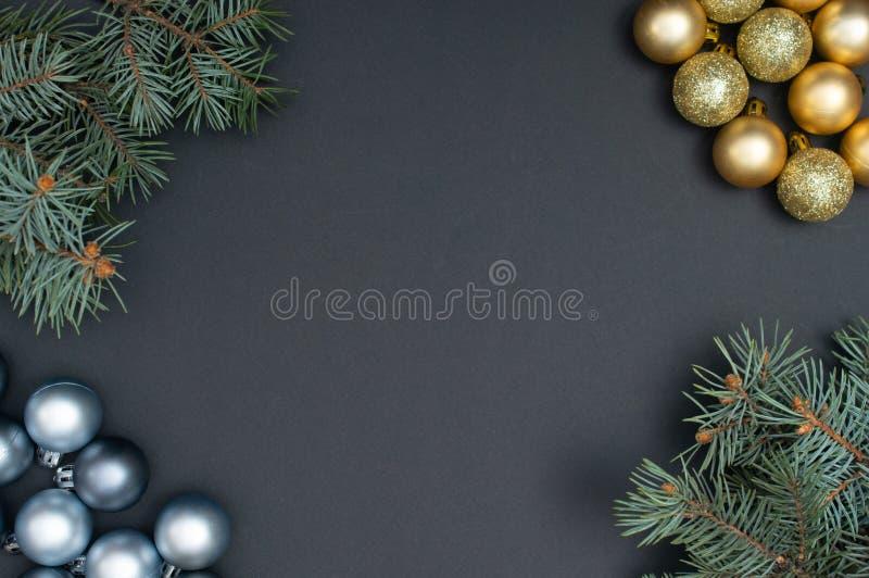 Natale multiplo argento e modello creativo della decorazione delle bagattelle dell'oro con i rami di pino sui precedenti neri fotografia stock