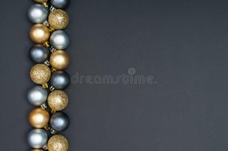 Natale multiplo argento e modello creativo della decorazione delle bagattelle dell'oro con lo spazio nero della copia e del fondo immagine stock