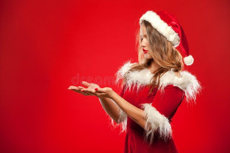 Natale, natale, inverno, concetto di felicità - donna sorridente in cappello dell'assistente di Santa con il contenitore di regal fotografia stock